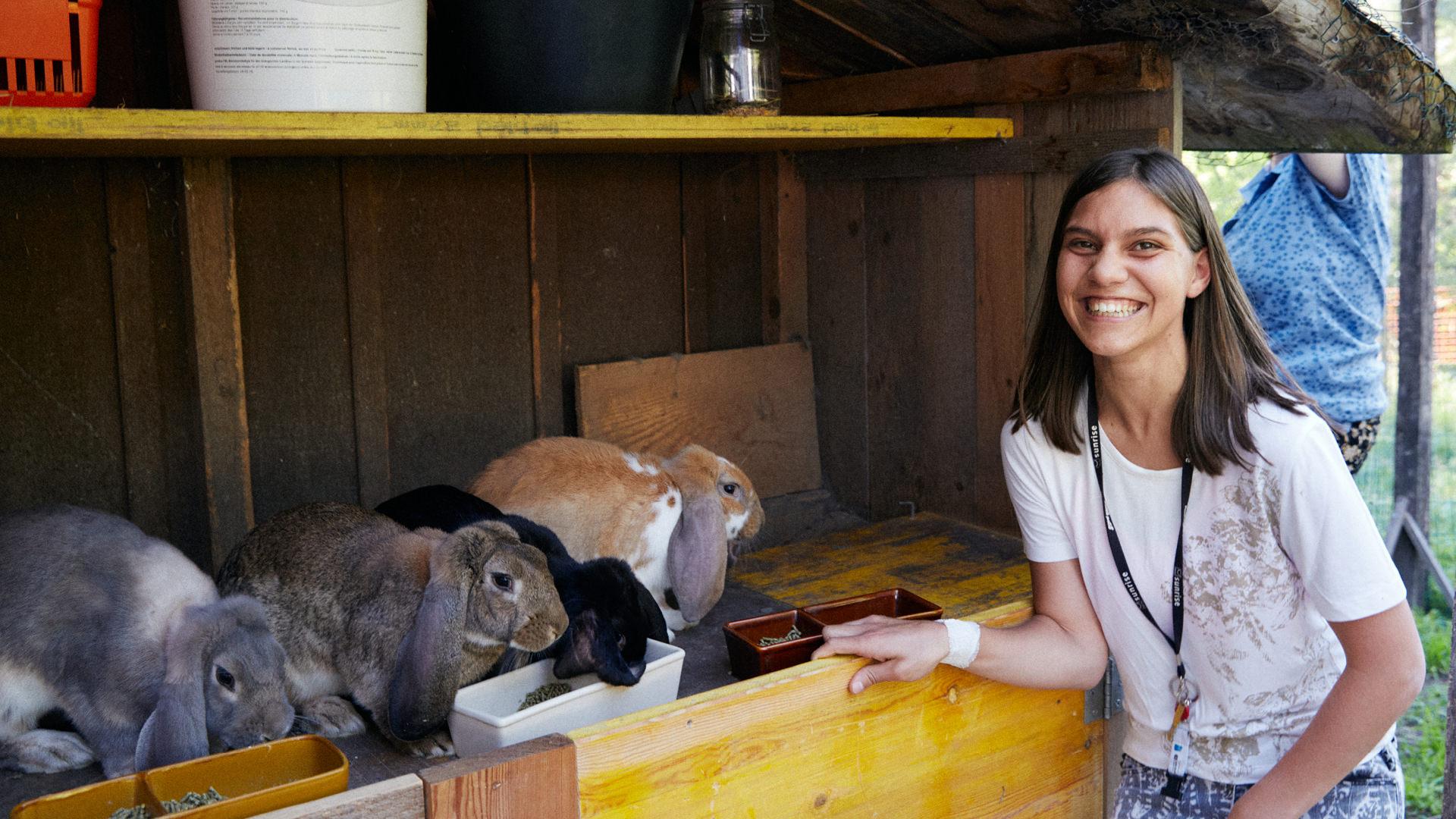 Mädchen füttert auf dem Biohof die Kaninchen.
