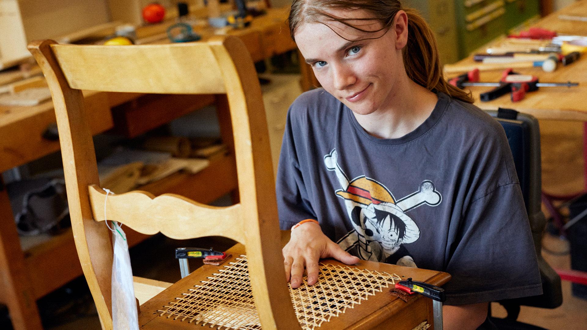 Frau arbeitet an Jonc-Stuhlgeflecht in der Schreinerei.