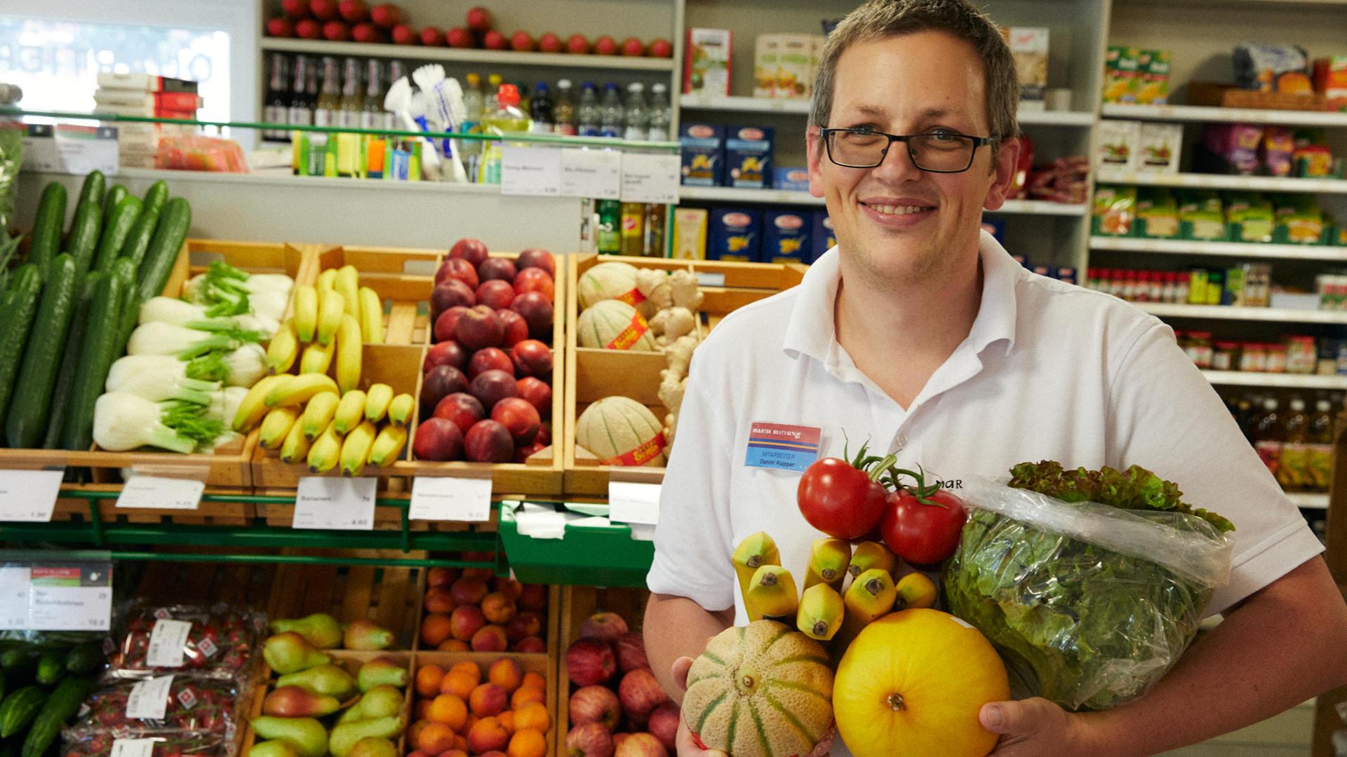 Mann füllt Gemüse- und Obstsortiment im Quartierladen Zum Feinen Martin auf.