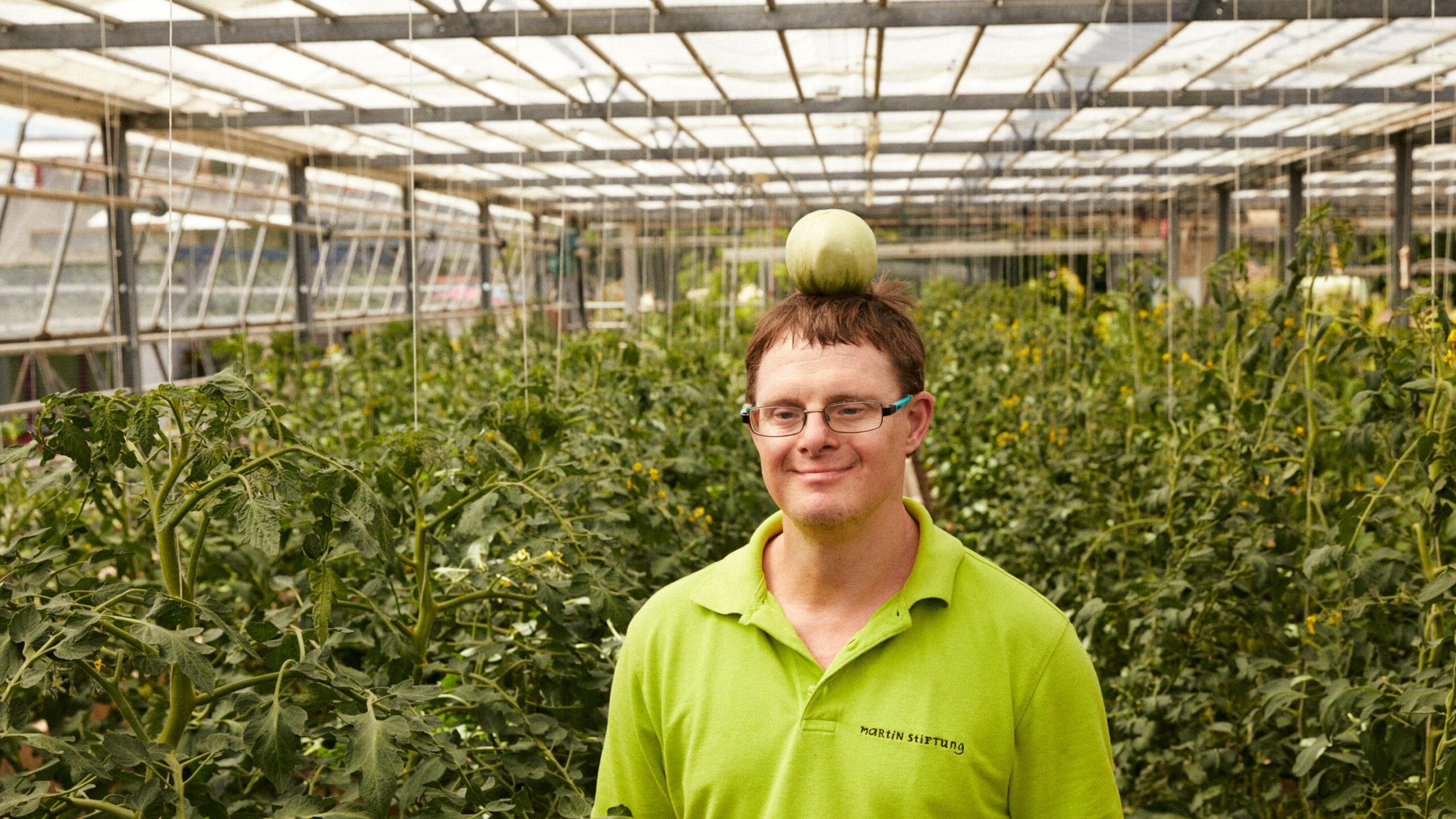 Mitarbeiter der Gärtnerei spielt Wilhelm Tell mit grüner Tomate auf dem Kopf.