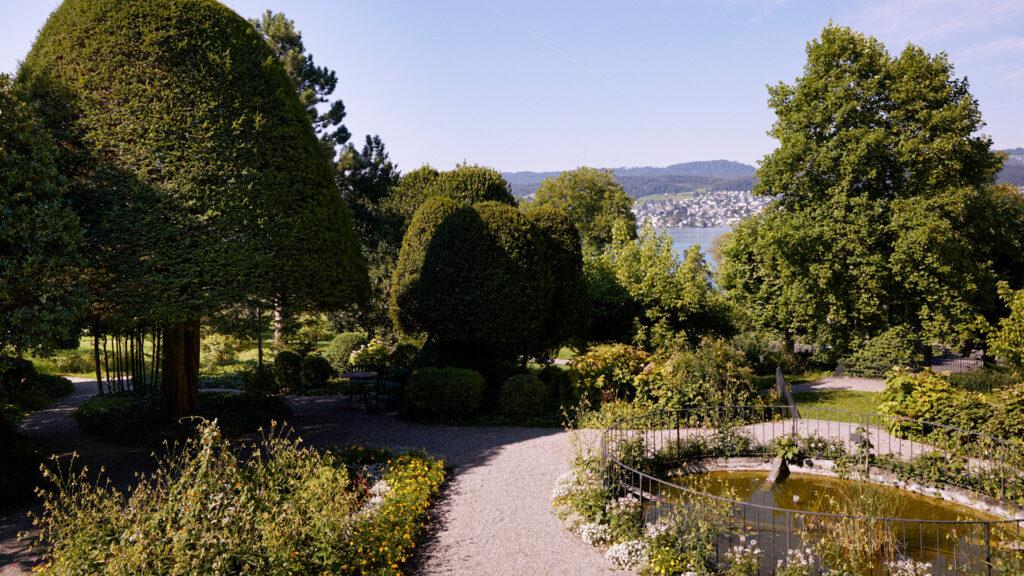 Barocke Parkanlage mit Teich, Blumenrabatten und geometrisch zugeschnittenen Bäumen und Sträuchern im Park Mariahalden.