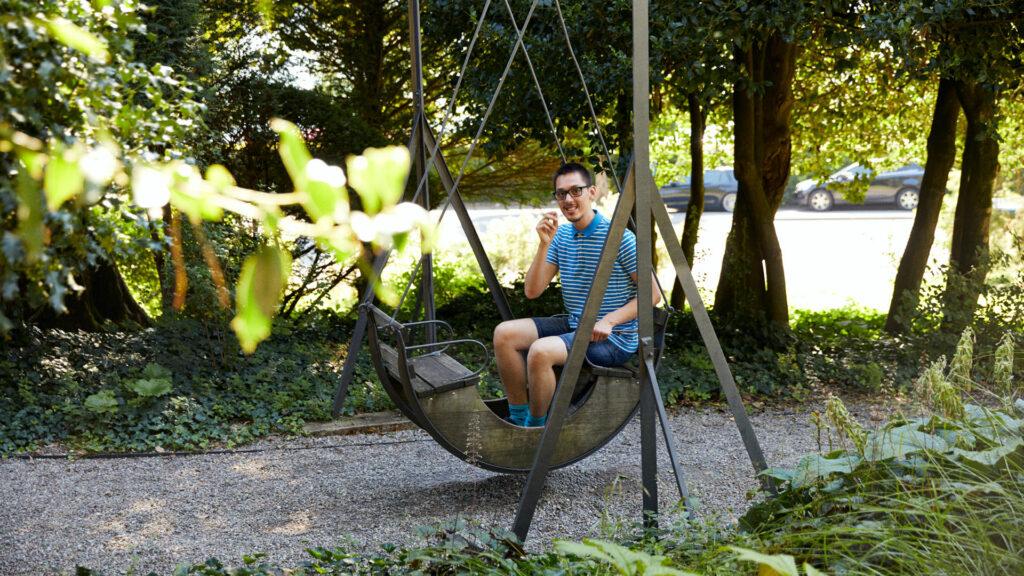 Bewohner der Martin Stiftung sitzt auf der historischen Schaukel im denkmalgeschützten Park Mariahalden.