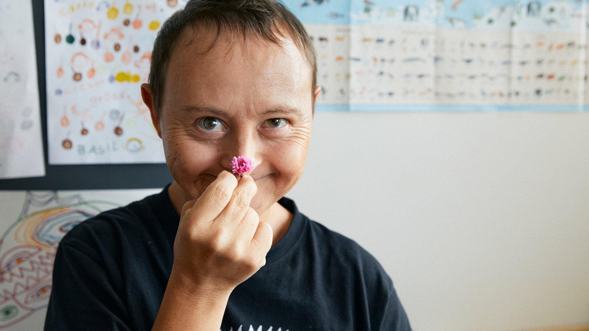 Bewohner der Martin Stiftung hält sich pinke Blüte an die Nase und lacht.