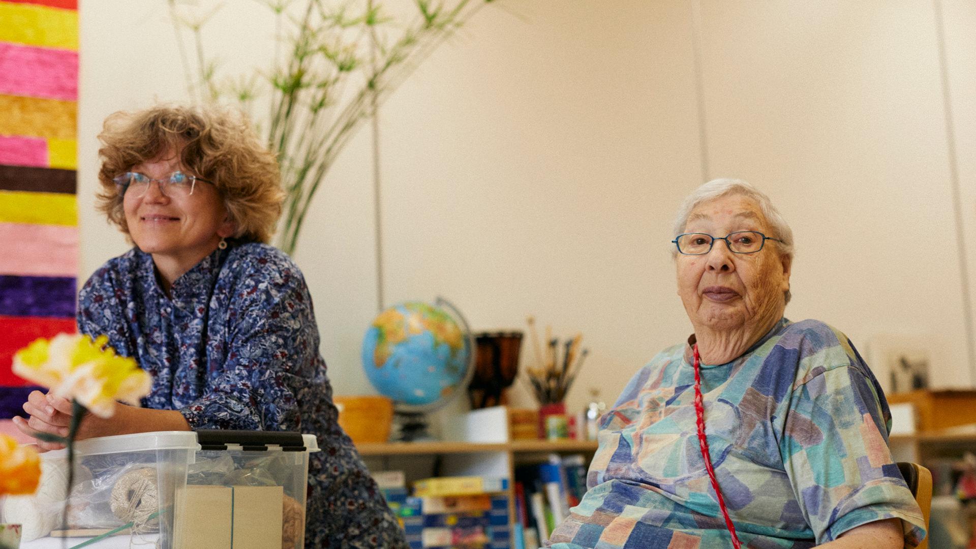 Leiterin vom Seniorenatelier mit einer Bewohnerin der Martin Stiftung. Sie schauen neugierig.