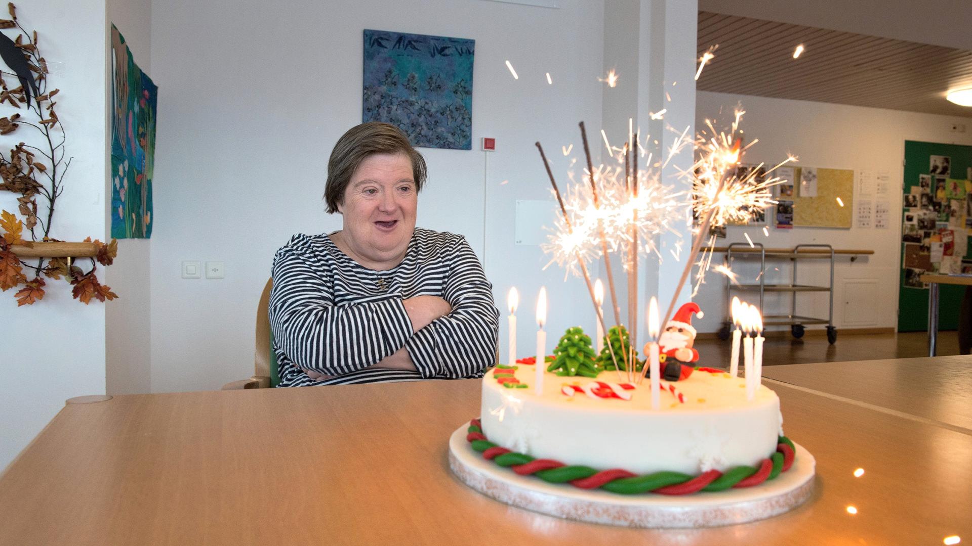 Bewohnerin der Martin Stiftung freut sich über ihren Geburtstagskuchen mit Wunderkerzen.