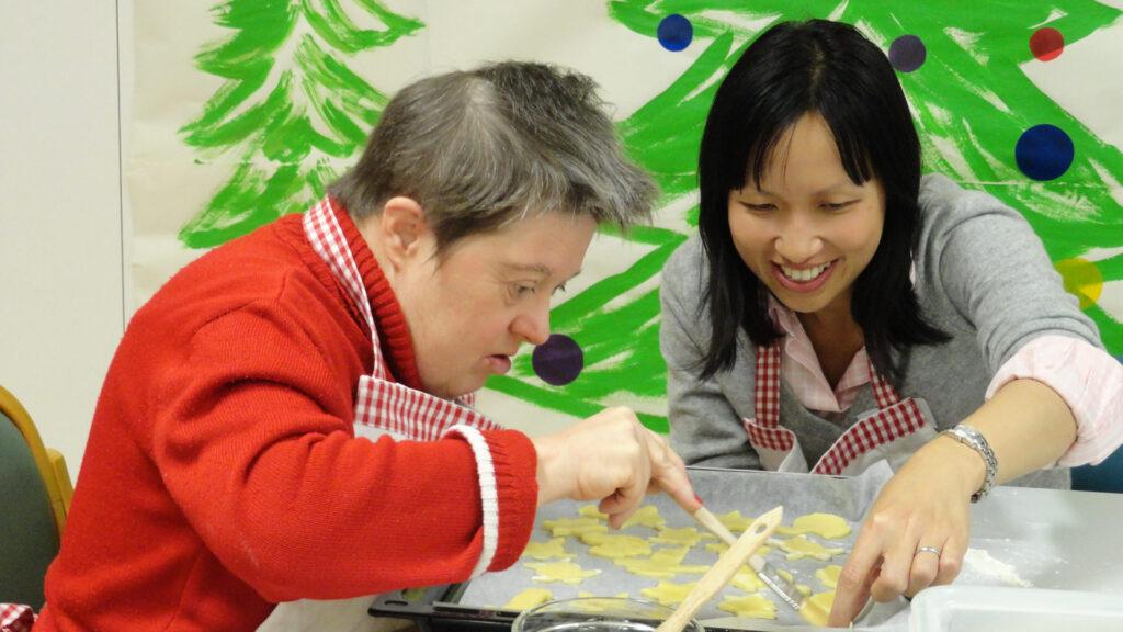 Freiwillige verbringt Zeit mit älterer Frau mit Behinderung in der Martin Stiftung.