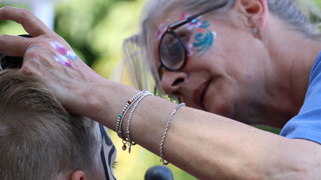 Kinderschminken bei Herbstfest. Eine Frau mit bunten Motiven im Gesicht malt die Kinder an.
