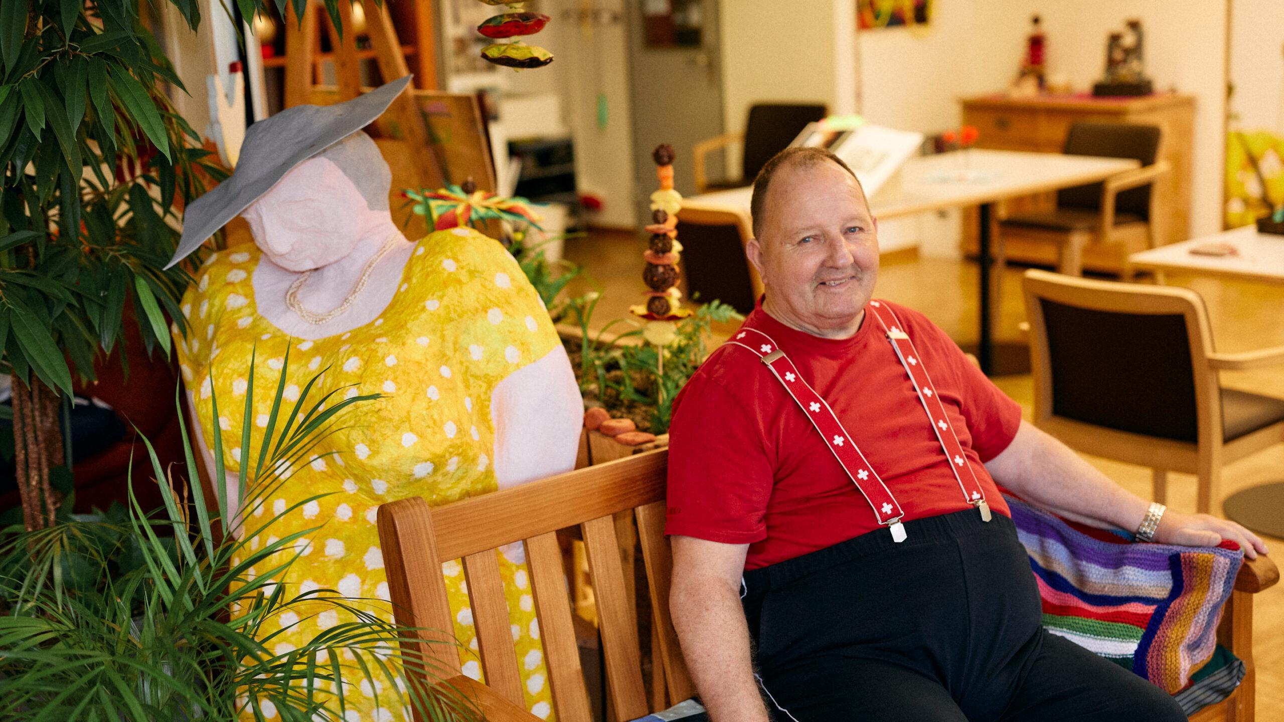 Bewohner der Martin Stiftung mit einer grossen Skulptur aus Pappmaché, einer Frau mit Hut und gelbem Kleid.