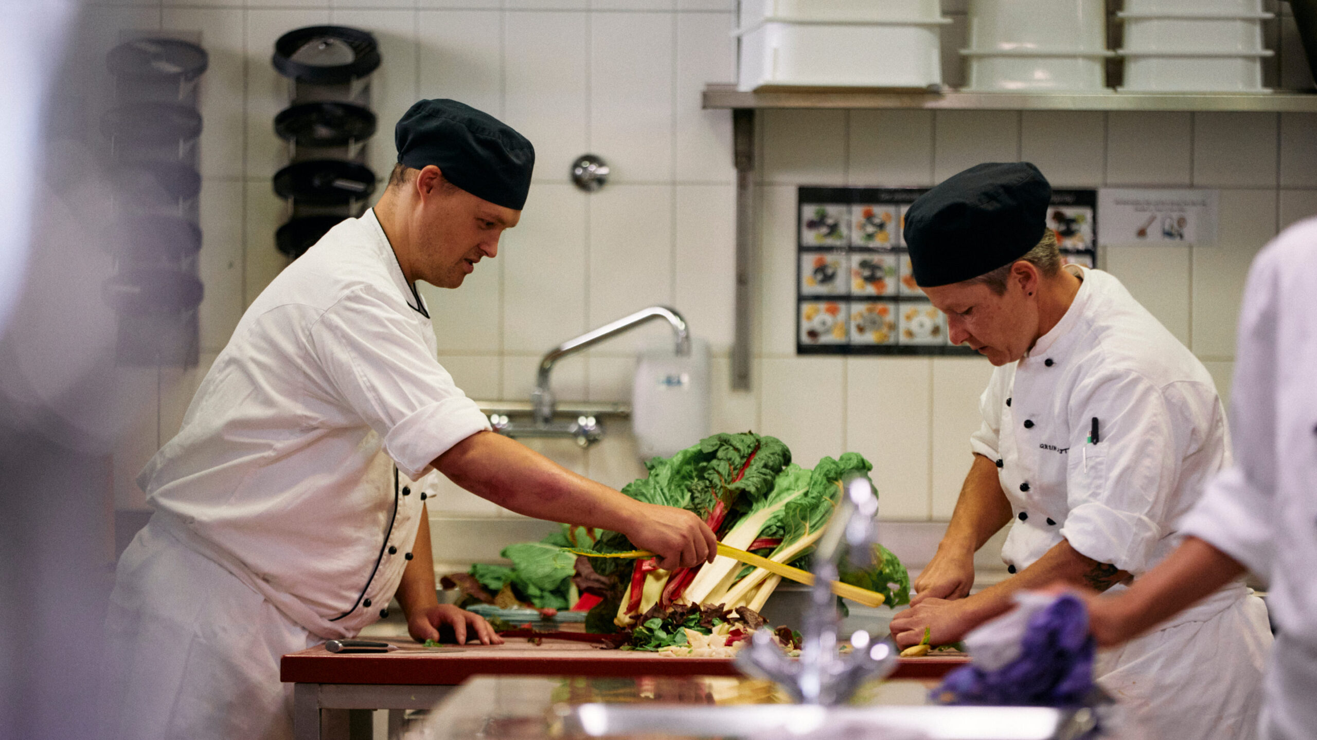 Mitarbeiter der Martin Stiftung macht eine PRA - praktische Ausbildung - in der Küche und rüstet zusammen mit Fachperson Gemüse vom eigenen Biohof.