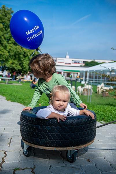 Ein kleines Kind sitzt in einem Laufwagen und spielt mit beim Kinderprogramm auf dem Herbstfest.