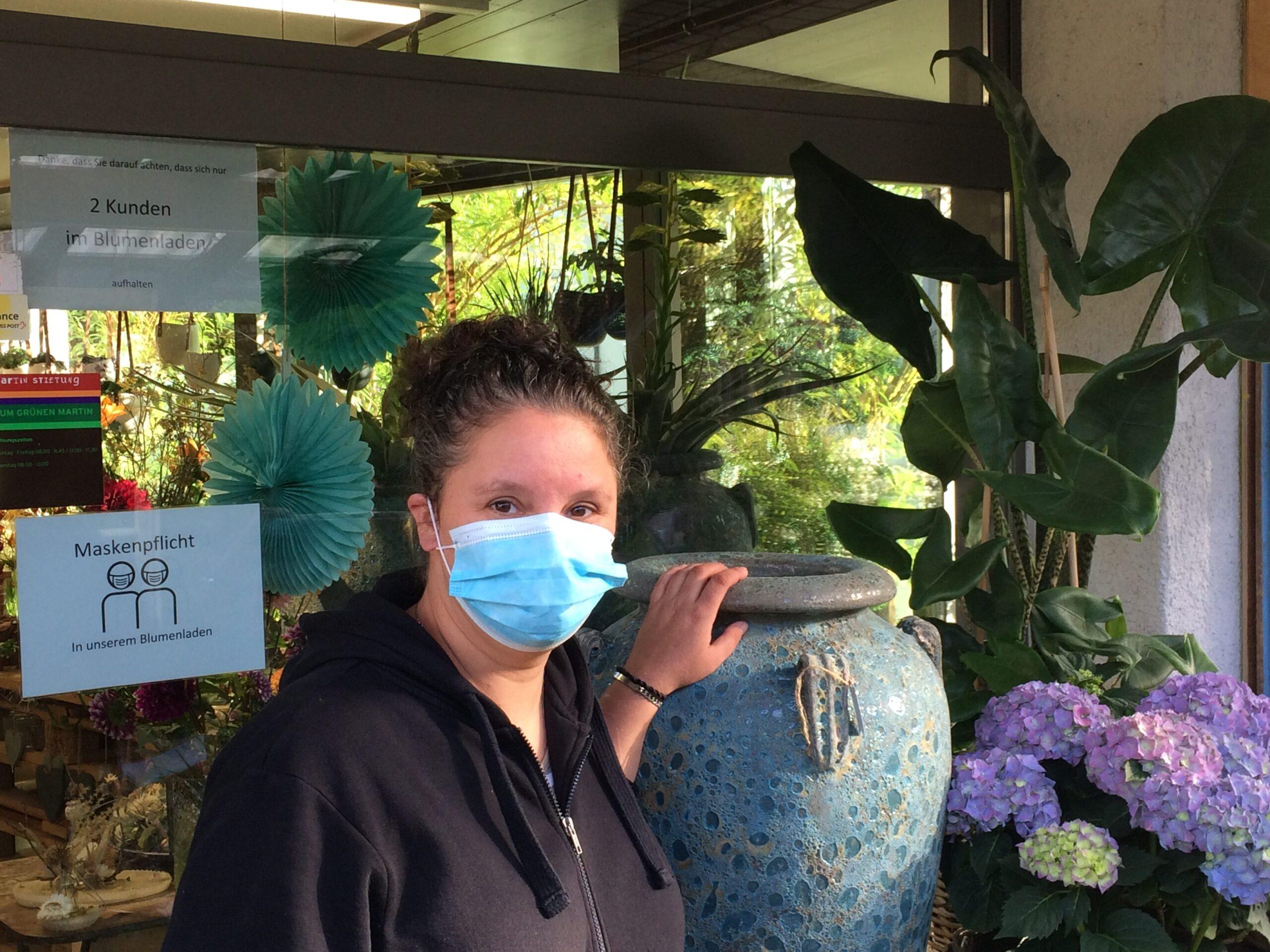 Frau mit Maske vor dem Blumenladen Zum Grünen Martin.