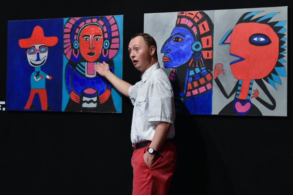 Beat Bucher beschreibt dem Publikum die farbstarke, figürliche Serie. Sie ist in Zusammenarbeit mit der Künstlerin Theres Berka entstanden.