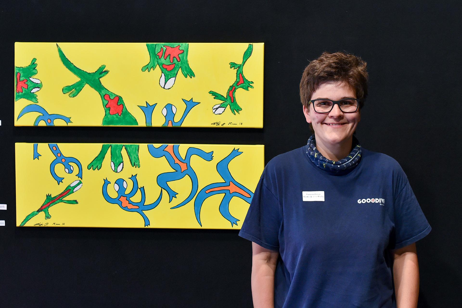 Bewohnerin und Künstlerin der Martin Stiftung neben ihren zwei Bildern bei der Ausstellung Eigenwillig.