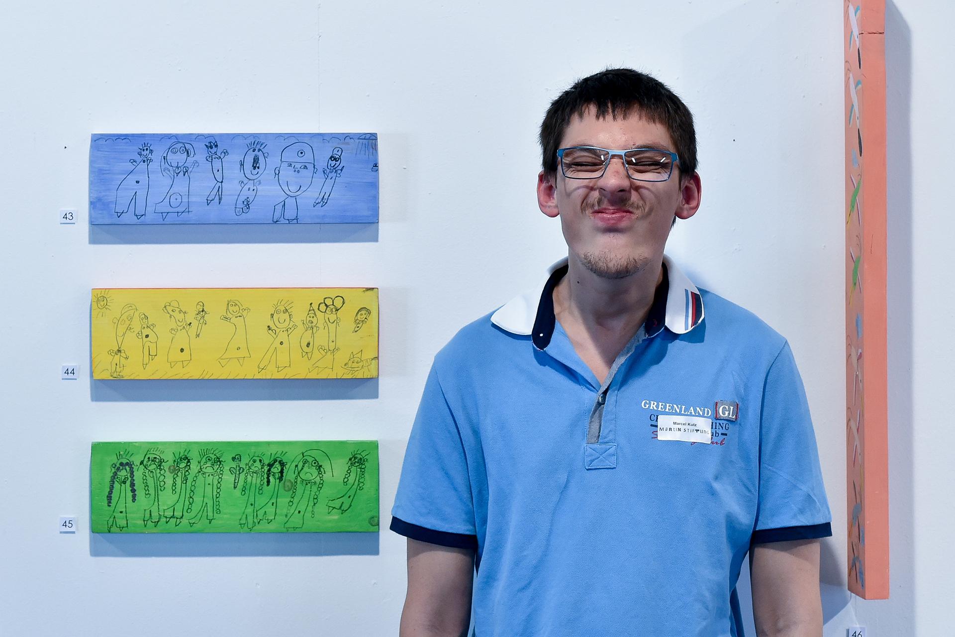Bewohner der Martin Stiftung neben seinen drei Zeichnungen auf farbiges Holz.