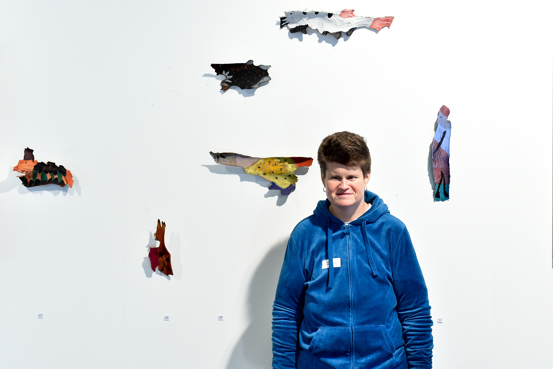 Künstlerin der Martin Stiftung neben ihren an der Wand aufgehangenen, bunten Skulpturen.