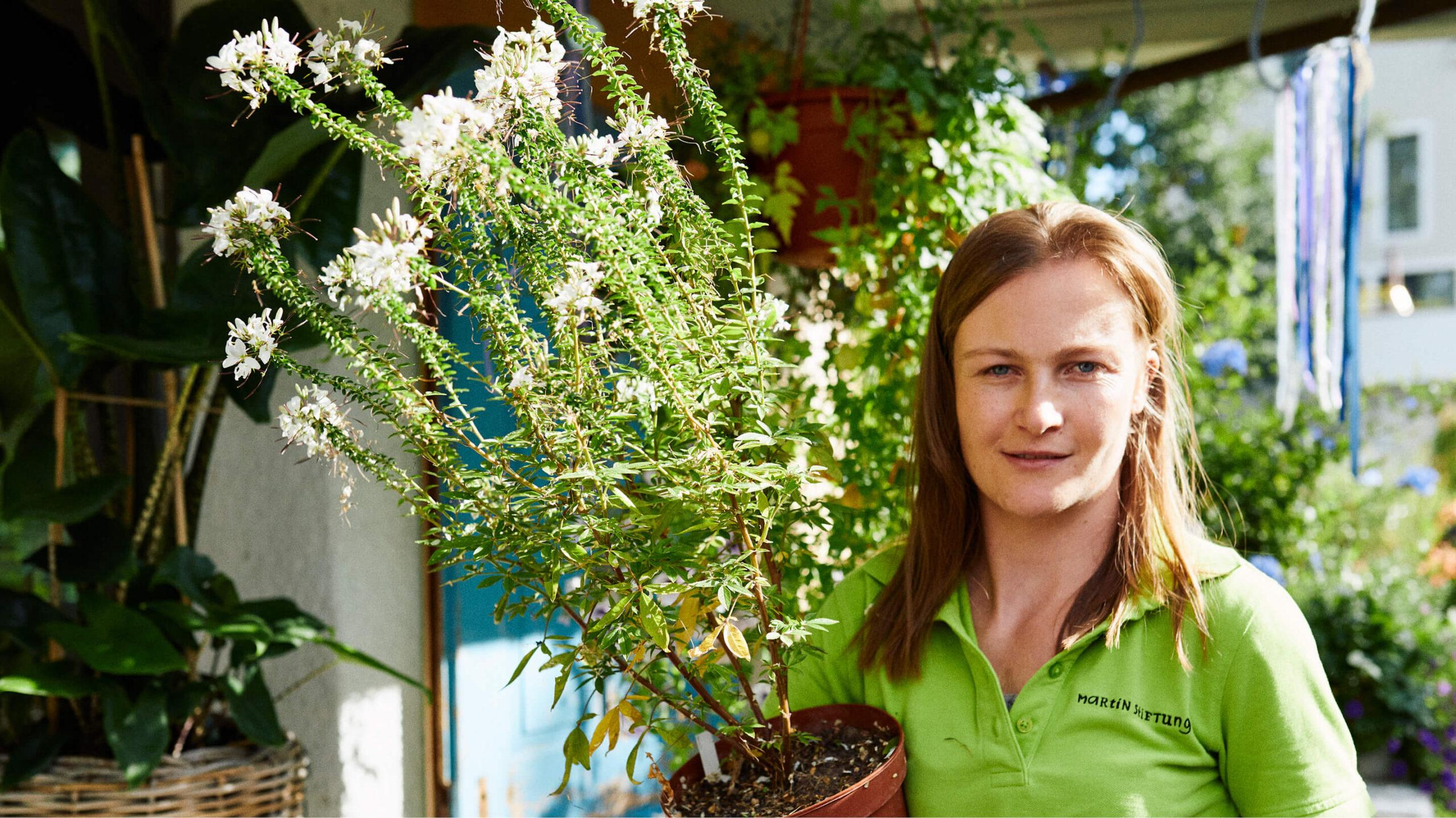Junge Frau mit Behinderung hält Pflanze im Arm und arbeitet in dem Blumenladen Zum Grünen Martin der Martin Stiftung