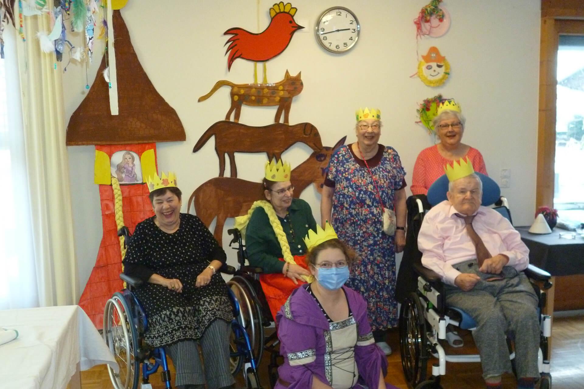 Wohngruppe der Martin Stiftung verkleidet für Fasnacht als Märchenkönige. Im Hintergrund ist Zeichnung von den Bremer Stadtmusikanten und Rapunzel an der Wand.