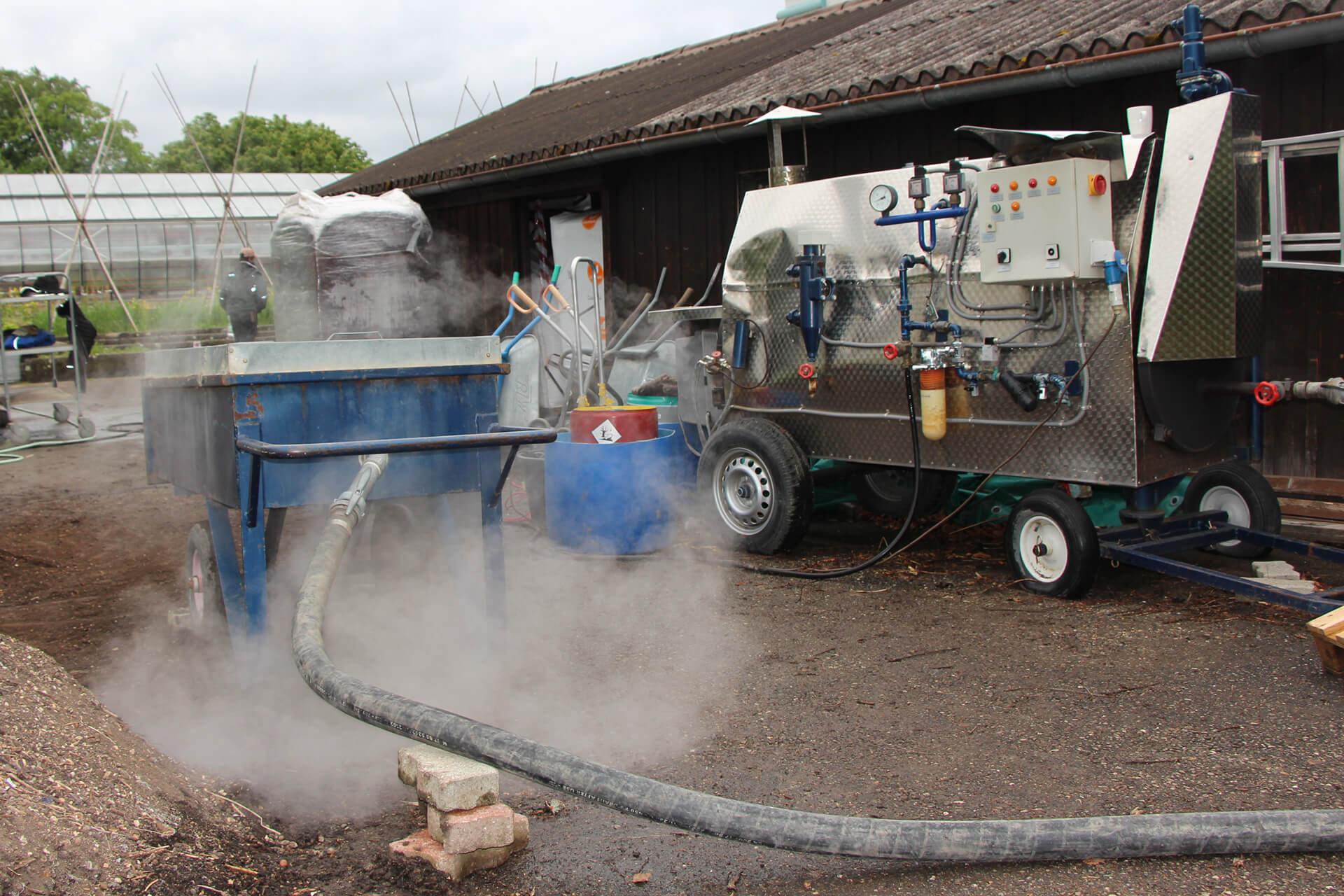Alte Maschine mit viel Dampf, um die Gartenerde zu erhitzen.