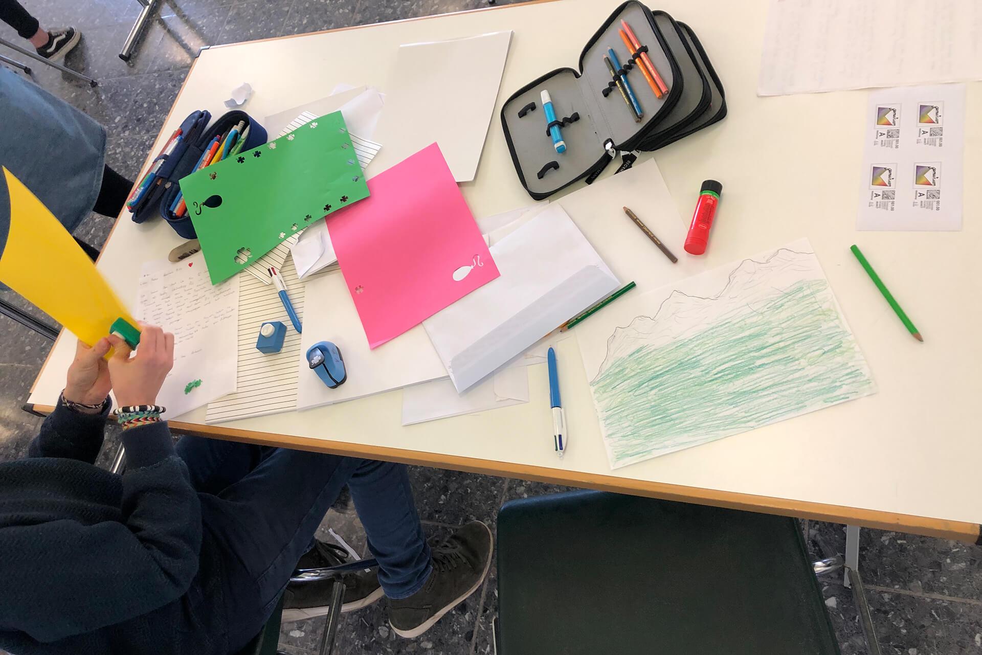 Schüler mit Schreibmaterial und Papier beim Gestalten eines Briefes.